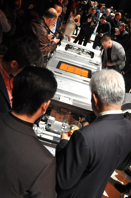 Guests study the base and battery grid of Faraday Future's FF 91 electric car on Jan. 3 at the World Market Center Pavilion. Photo by Buford Davis   Las Vegas Business Press