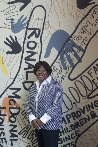 Eva Martin stands by a mural at her Craig Road shop.