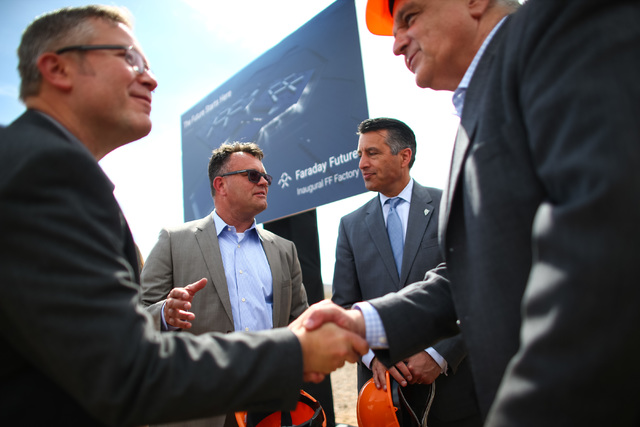 Faraday Future Vice President of Manufacturing Dag Reckhorn, center left, and Gov. Brian Sandoval speak following the groundbreaking for the planned 900-acre manufacturing site in North Las Vegas  ...
