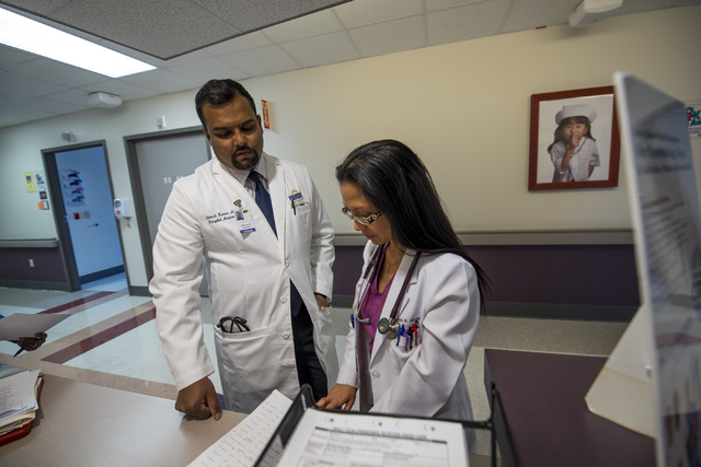 Dr. Shivesh Kumar, left, chief hospitalist at Spring Valley Hospital Medical Center, reviews a file with fellow hospitalist, Dr. Fema Aquino at Spring Valley Hospital Medical Center on Thursday, J ...