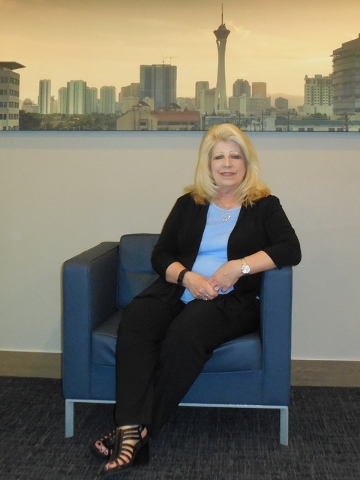 Sue Kwasneski sits against a backdrop of Las Vegas in the company's office.