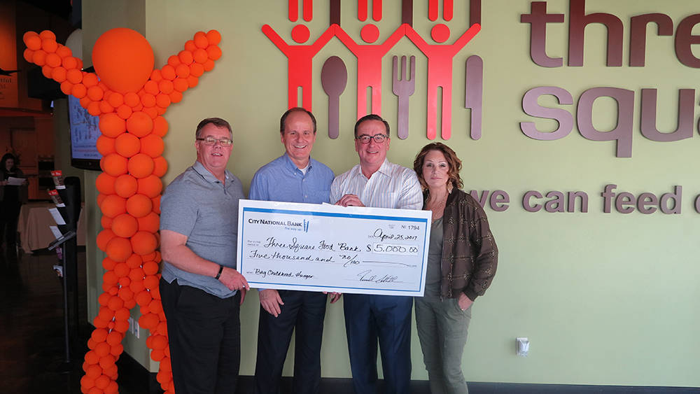 Larry Scott (l-r), CFO of Three Square, Paul Stowell with City National, Brian Burton, CEO of Three Square, and Diana Bennet with the Bennet Family Foundation take part in City National's donati ...