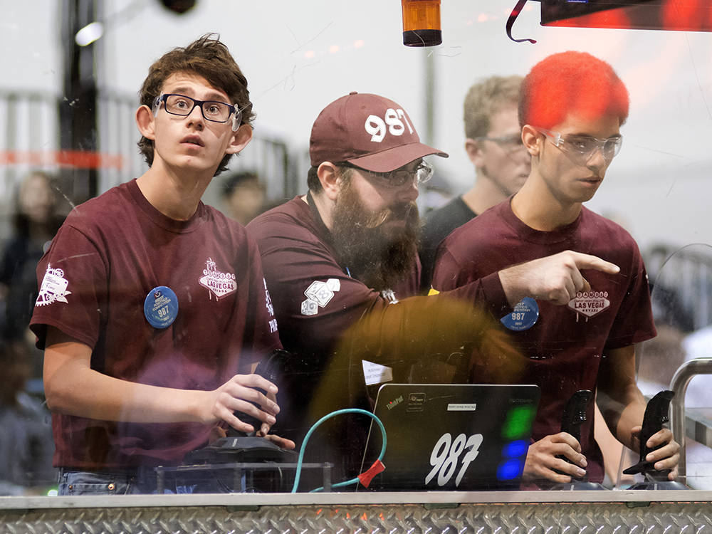 Cimarron-Memorial High School students Arnold Erasmus, left, and Kevin Hjelstrom, right, are shown with their coach Steve McKinney during the FIRST Robotics regional competition in the Cashman Eve ...