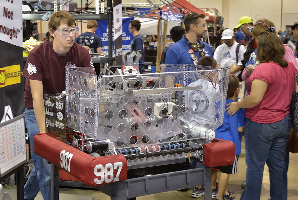 Cimarron-Memorial High School student Lourens Erasmus wheels his team's robot from the staging area to the arena during the FIRST Robotics regional competition in the Cashman Event Center April  ...