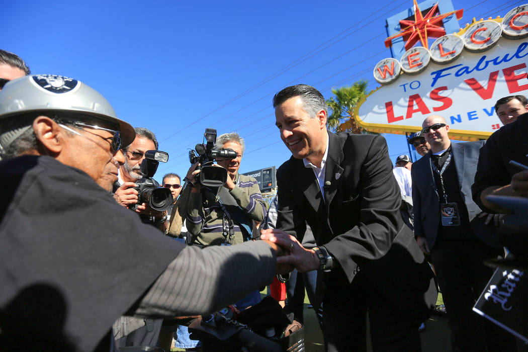 Nevada Gov. Brian Sandoval, center, shakes the hand of 75-year-old Raiders fan Melvin Smith during a draft party for the Raiders at the welcome to Las Vegas sign April 29. (Brett Le Blanc Las Vega ...