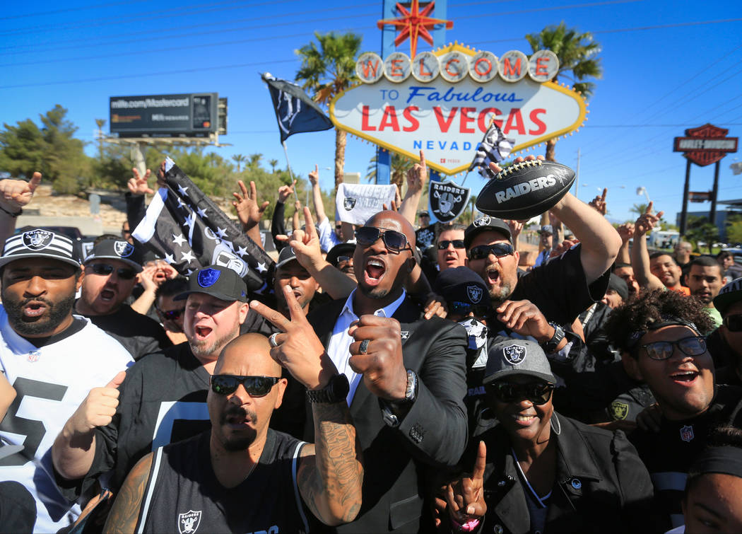 Akbar Gbaja-Biamila, center, who played for the Raiders in 2003 and 2004, leads a Raiders chant during a draft day party for the Raiders at the welcome to Las Vegas sign. (Brett Le Blanc Las Vegas ...