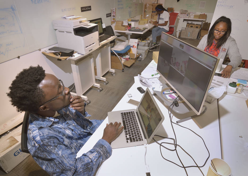 Chief technology officer Kwame Ampem, left, production manager LaTasha Darden, background, and CEO Tamar Lucien from a company called Mental Happy work at the RedFlint Experience Center at 300 S.  ...