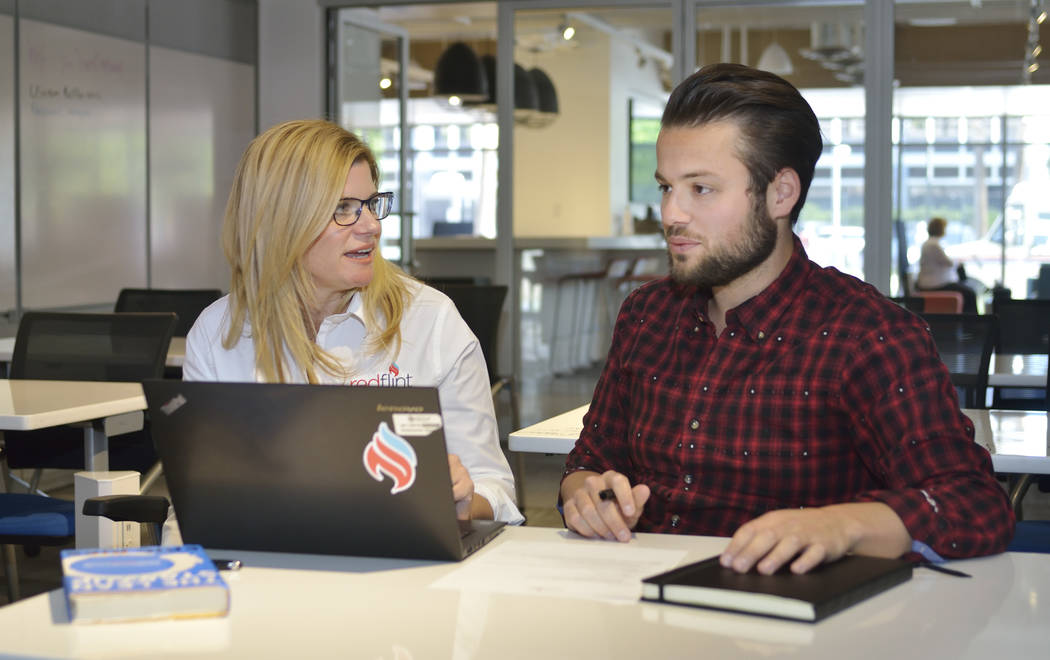 Stephenie Golden, vice-president of enterprise resource management for the University of Phoenix, left, helps Fred Loguidice create a framework for his new business at the RedFlint Experience Cent ...