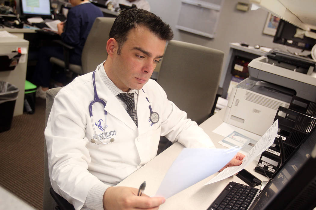 Fadi Braiteh, MD of Comprehensive Cancer Centers of Nevada, looks over paperwork.