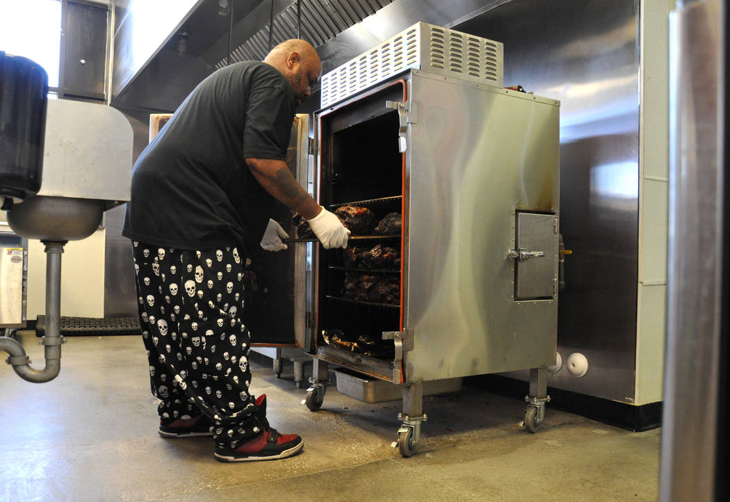 Michael Harris, co-owner of Tennesseasonings, removes roasted pork butt from the smoker for the day's service, May 23. Photo by Buford Davis / Las Vegas Business Press