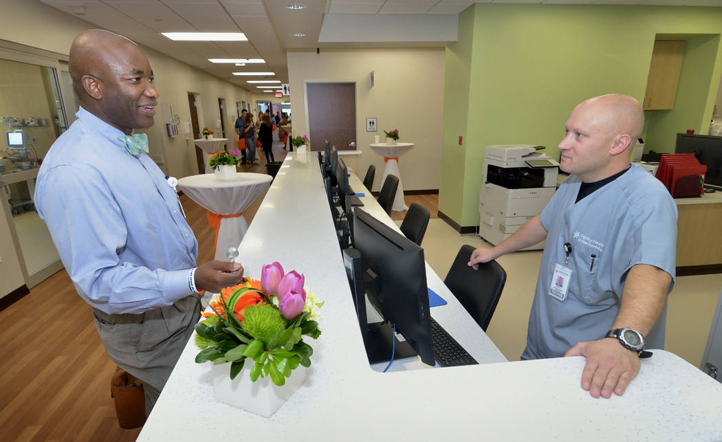 Dr. Chike Nzerue, chief medical officer at Dignity Health, left, talks with emergency room technician Gene Sonnenburg at the Dignity Health-St. Rose Dominican Blue Diamond Campus, which opened in  ...