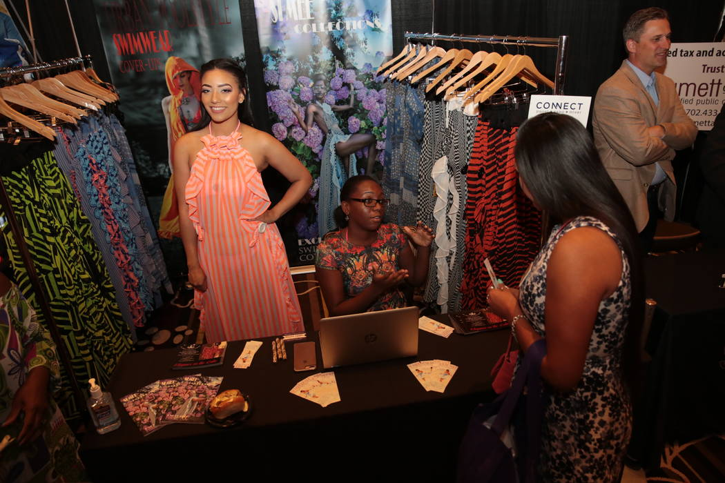 Taylor Odum shows off bathing suit cover-up fashion by Si Mee Collections while Chaize Macklin speaks to a chamber member during the Henderson Chamber of Commerce's CONNECT Expo+Panel+Mixer even ...