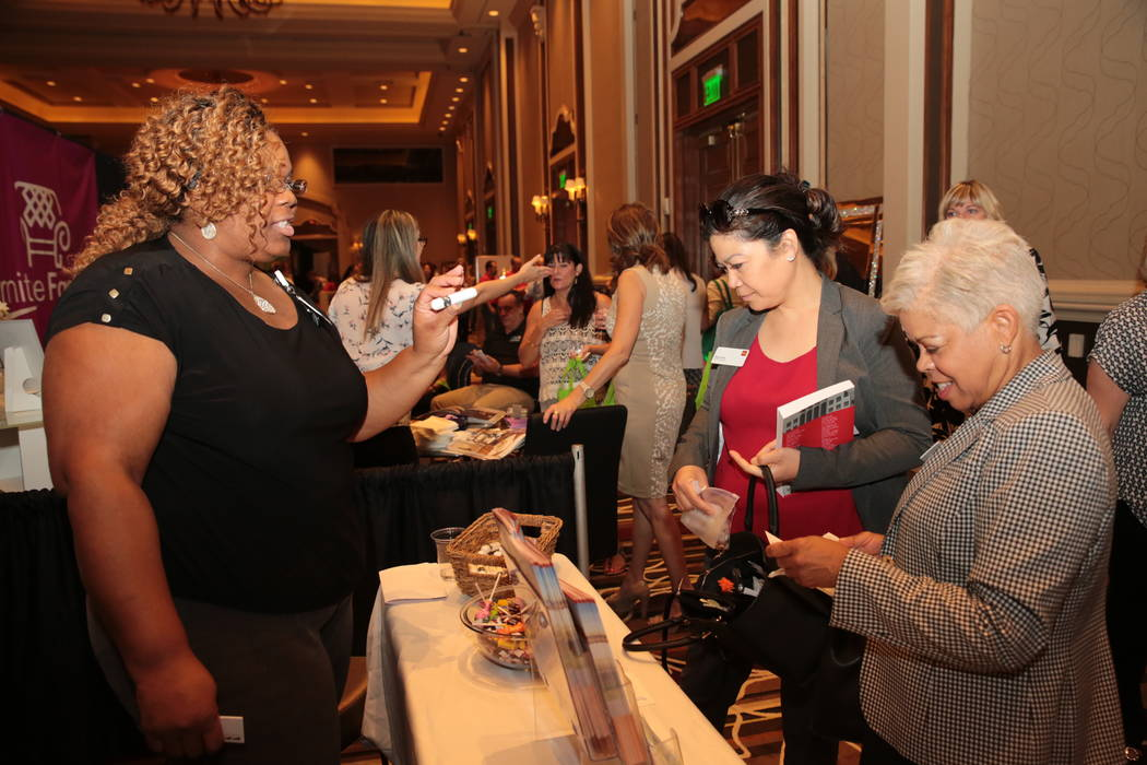 From left, Celyse Nsubuga, community health worker with Dignity Health, speaks to Pearl Irwin, business specialist with Wells Fargo, and Verena Culpepper, also with Wells Fargo, during the Henders ...