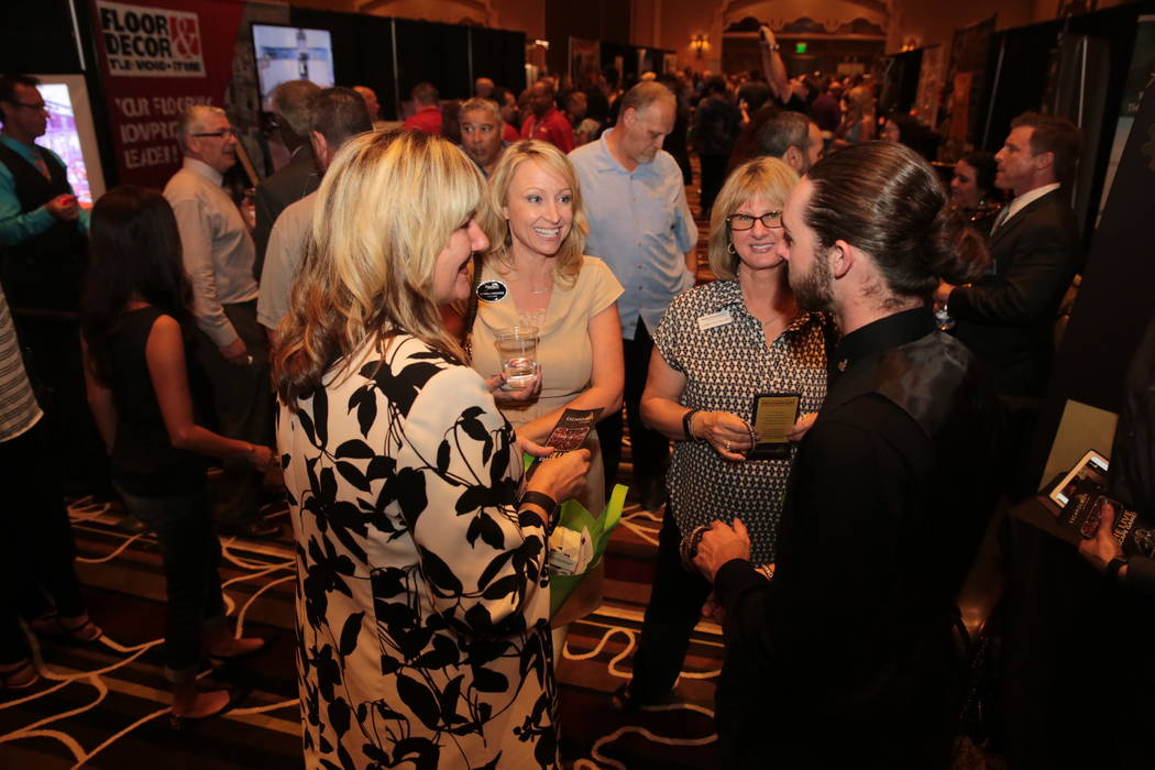 From left, Christina Weick of Bank of Nevada, Tamra Coulter of Signature Real Estate Group and Lisa Molchon from Mutual of Omaha Bank speak to Ryan Doyle, game master at Escapology during the Hend ...