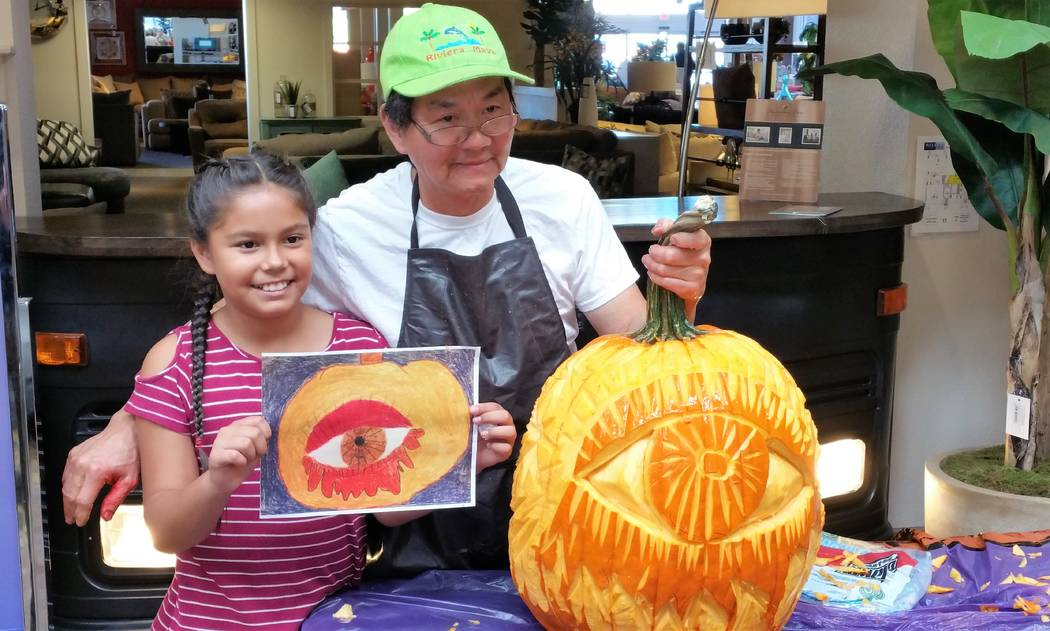 At a Chanh Boupha pumpkin carving event held in the Atrium at Walker Furniture on Oct. 28, chef Boupha carved first-place winner, fourth-grader Briana Magdaleno's drawing. (Courtesy)