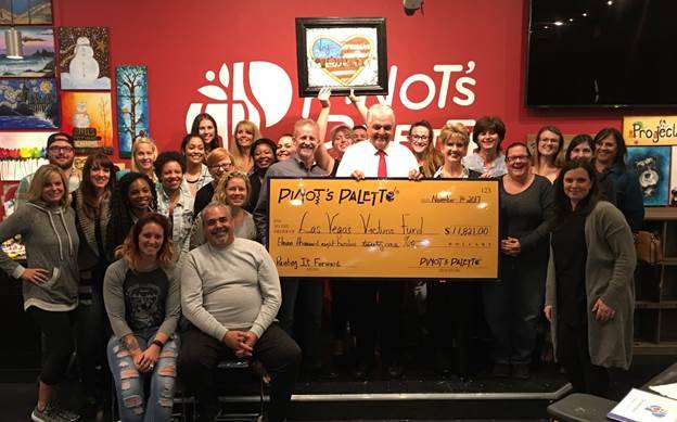 Pinot's Palette owners, Reed and Judy Alewel, left, front row, and their staff, present Clark County Commissioner Steve Sisolak a $11,821 check for the Las Vegas Victims' Fund on Nov. 7. (Cour ...