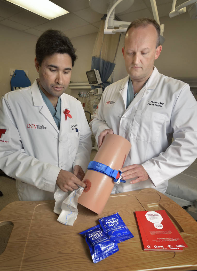 Trauma surgeon Dr. Syed Saquib, left, and Dr. Douglas Fraser, vice chief of trauma at UMC, demonstrate a Stop the Bleed training kit at the UMC Trauma Center. (Bill Hughes Business of Medicine)