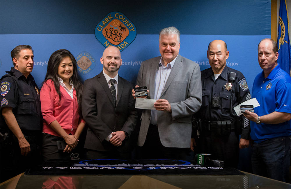 Boulder City-based Fisher Space Pen Co. gave a two $5,000 checks to The Las Vegas Victims Fund and The Injured Police Officers Fund of Nevada. From left to right, Sgt. Rom Rainey, Minddie Lloyd, ( ...