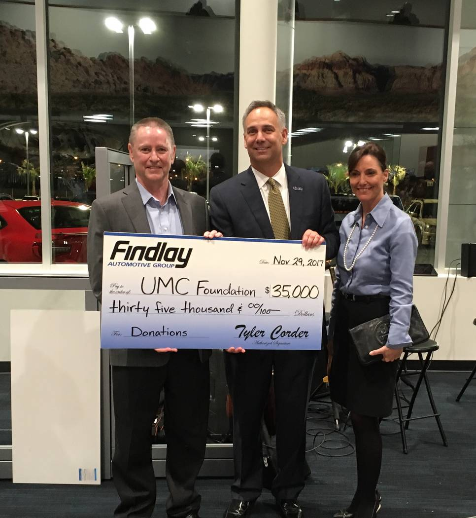 Findlay Automotive Group CFO Tyler Corder, left, presents a check for $35,000 to Mason Van Houweling, UMC CEO; and Marcia Turner, chief administrative officer for UMC. (Courtesy)