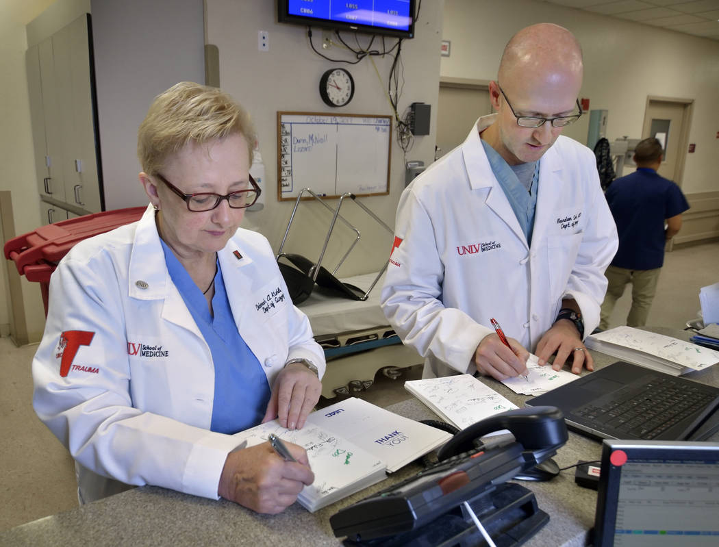 Dr. Deborah Kuhls, medical director of the UMC Trauma Center intensive care unit, and Dr. Brandon Snook, sign thank-you cards to the people who gave donations and support to the UMC Trauma Center  ...