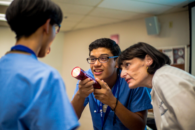 Dr. Laura Culley, associate dean for Health Policy and Community Affairs at the UNLV School of Medicine, teaches students how to look at tonsils during an annual CampMED at UNLV. (Elizabeth Brumle ...