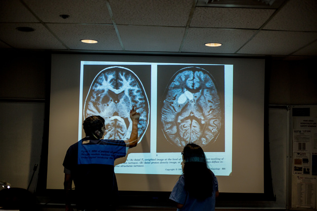 Dr. Kalyan Tatiney, left, points at different parts of a brain to CampMed participant Khaya Mae Tawatao at UNLV in Frank and Estella Beam Hall. (Elizabeth Brumley Business of Medicine)