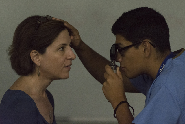 Student Jose A. Leon, right, examines Lisa Rosenberg, assistant professor of geriatrics with Roseman University of Health Sciences, with an ophthalmoscope, viewing her retina and blood vessels. (J ...