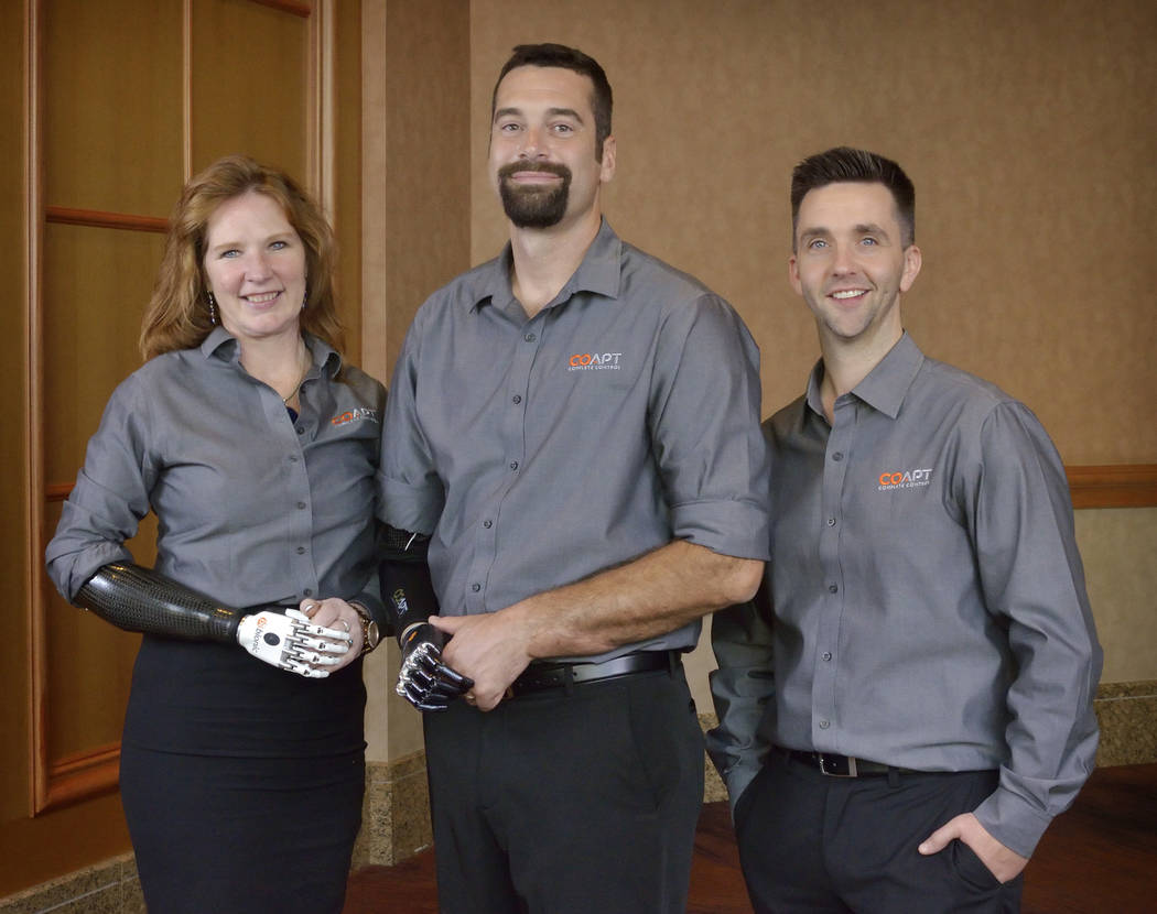 Jodie O'Connell-Ponkos, left, Glen Lehman, a consultant with Coapt, center, and Coapt co-founder and CEO Blair Lock are shown at the American Orthotic & Prosthetic Association convention at the  ...