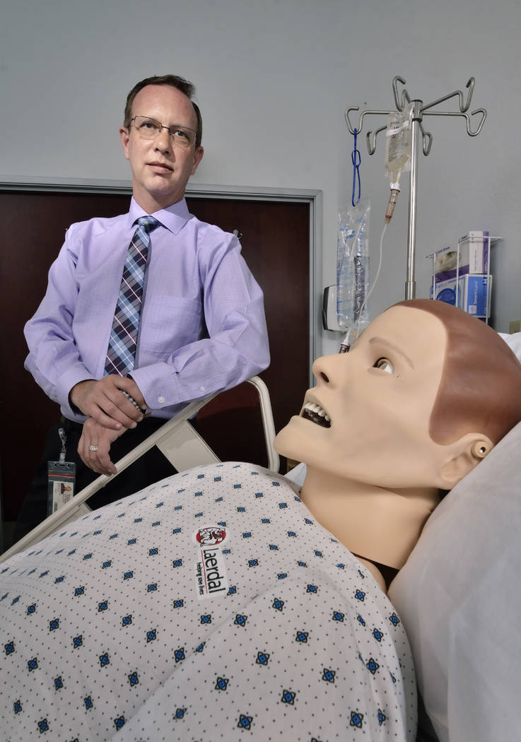Delos Jones, director of clinical resources at Roseman University of Health Sciences, is shown with Sim Man, a computerized mannequin. (Bill Hughes Las Vegas Business Press)