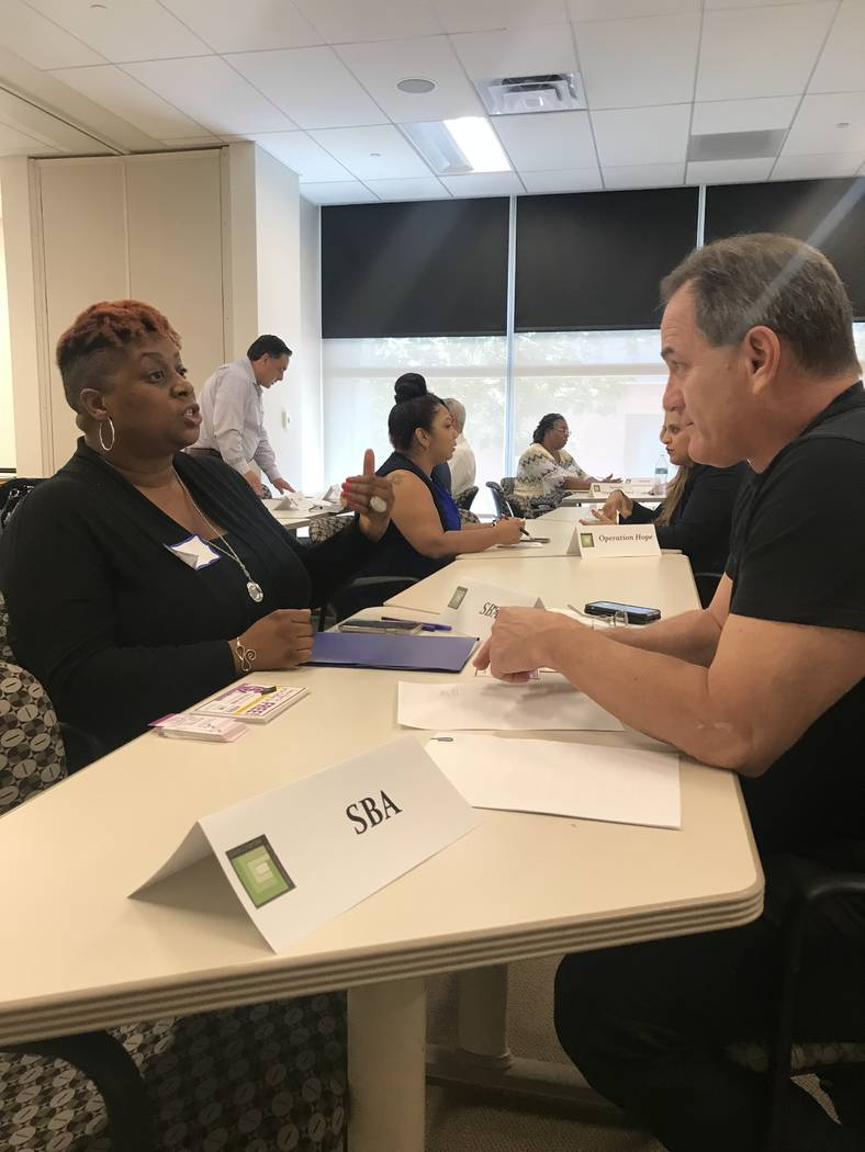From left, Rhea Watson, owner of Scholarship Solutions, and Joseph Amato, district director of the Nevada office of the Small Business Administration, discuss finances.