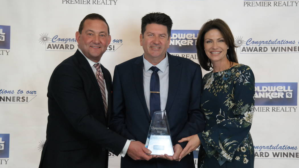 Coldwell Banker Premier Realty Chairman and CEO Bob Hamrick, left, poses with Alan Sheleheda, who received a Diamond Society Award at a Feb 20 event. Molly Hamrick, right, is the company's chief o ...