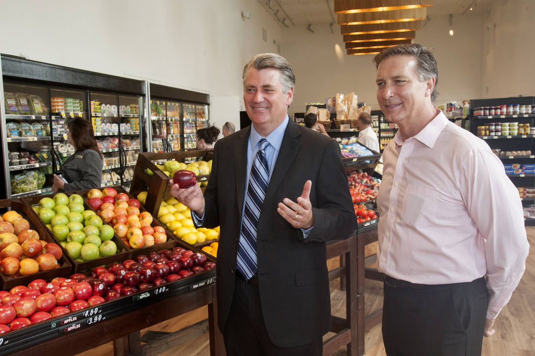 Patrick Parker, Raintree Investment Corp. president, left, and Doug McPhail, Seasons grocery store general manager talk on opening day for the market, June 21, 2016, in MonteLago Village at Lake L ...
