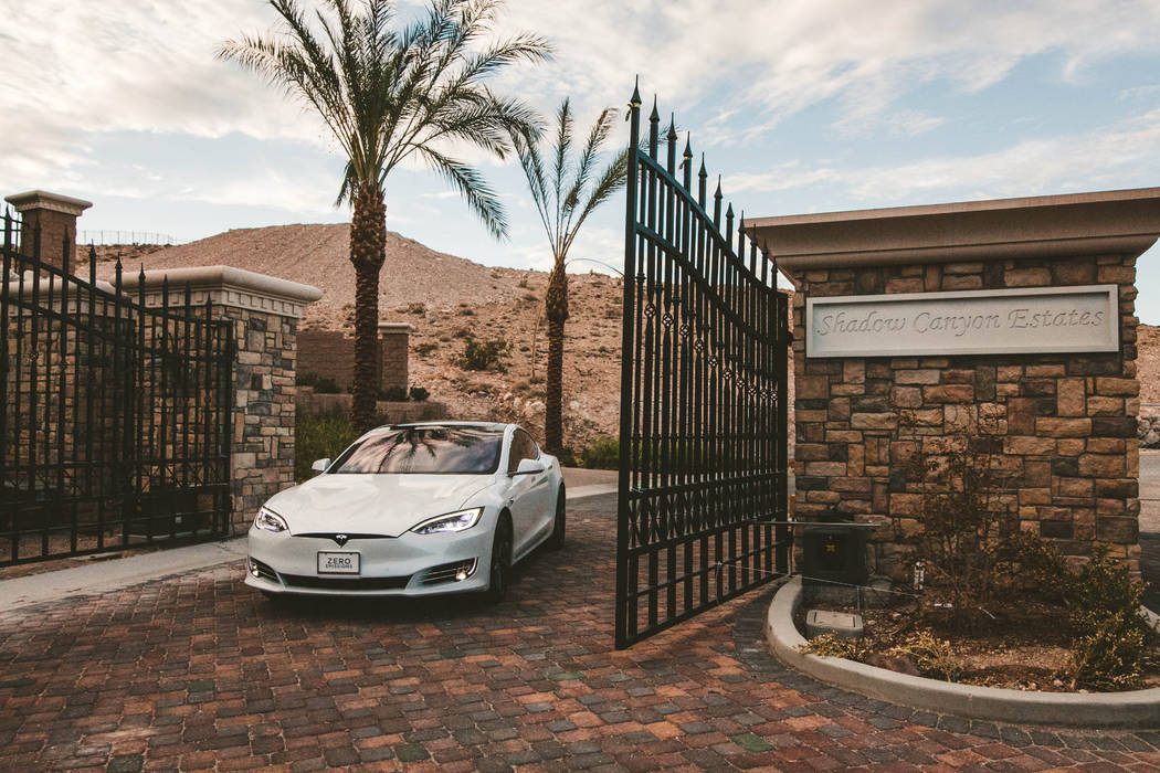 A private gate at the front of the property allows access up a sloping driveway to a six-car ga ...
