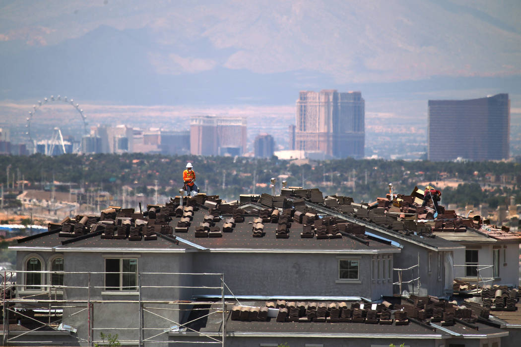 Workers are seen on the roof of an under-construction house in the Cadence master-planned commu ...