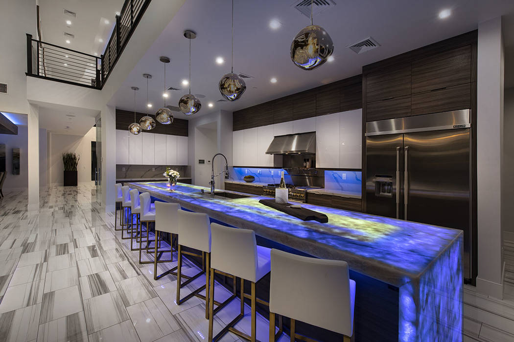 The gourmet Jenn-Air Pro kitchen features Onyx under light waterfall counter tops. (Synergy Sot ...