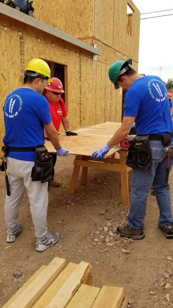 City National Bank colleagues helped cut wood panels for the roof for a Habitat for Humanity La ...