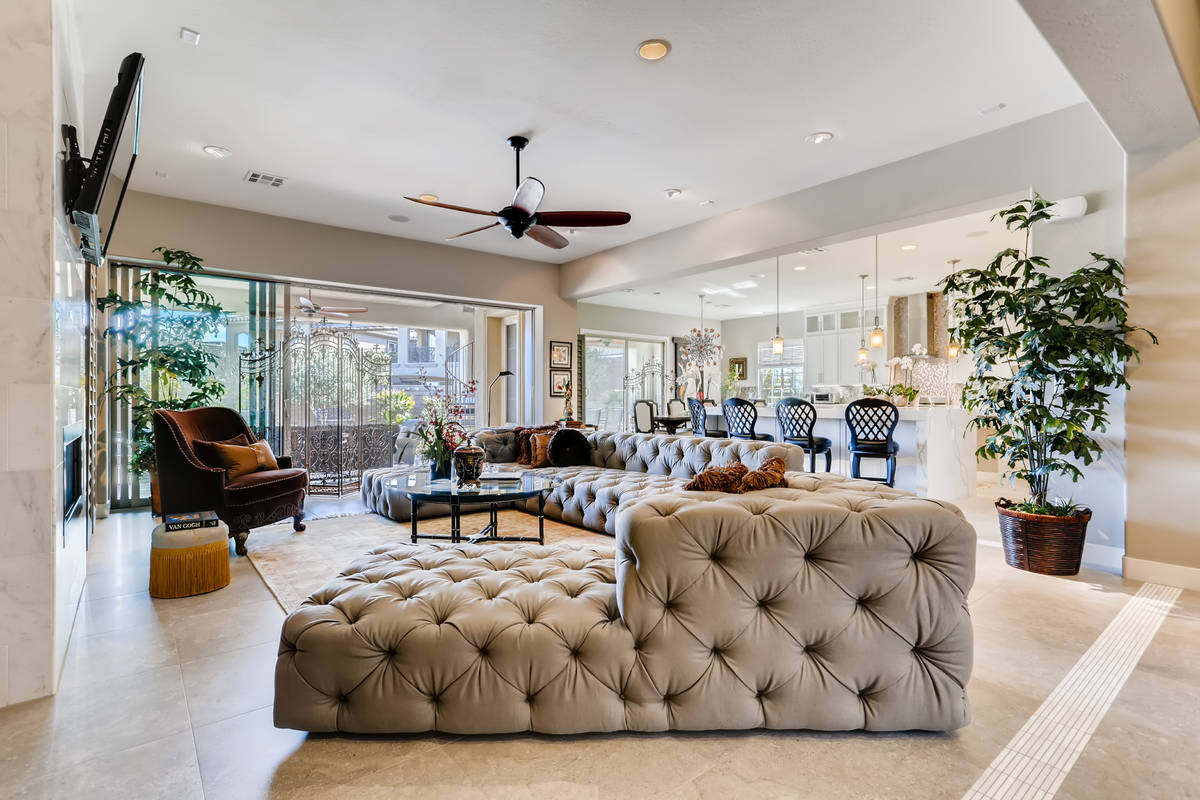 The living room is adjacent to the kitchen and leads to the pool area. (Realty One Group)