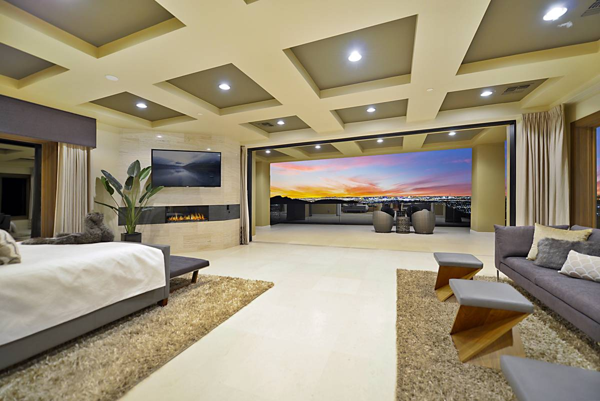 The upstairs master suite features a disappearing wall that allows for sweeping views of the La ...