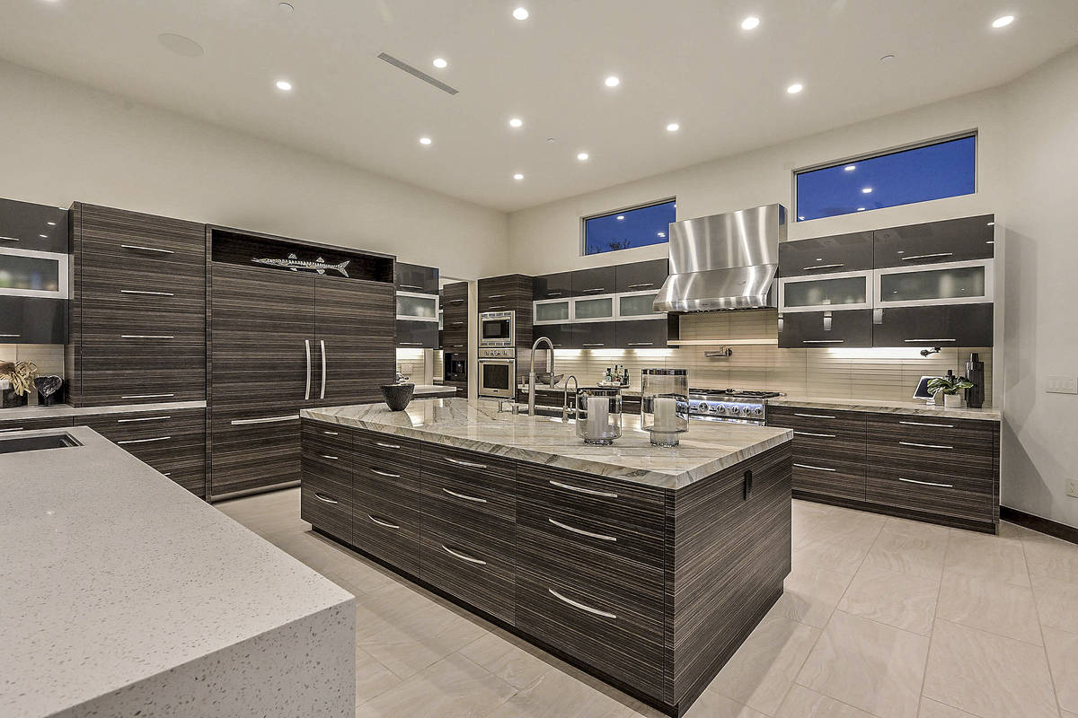The kitchen features plenty of custom cabinets, Brazilian quartzite waterfall counters and a la ...