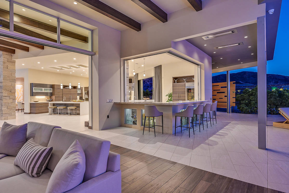 The indoor/outdoor bar extends to the patio that has an outdoor kitchen, pool and spa and seati ...