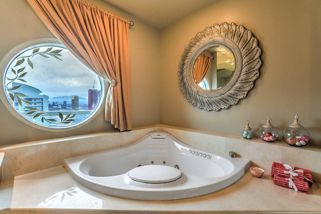 The master bathroom's soaking tub has sweeping views of the Las Vegas Strip from the top floor ...