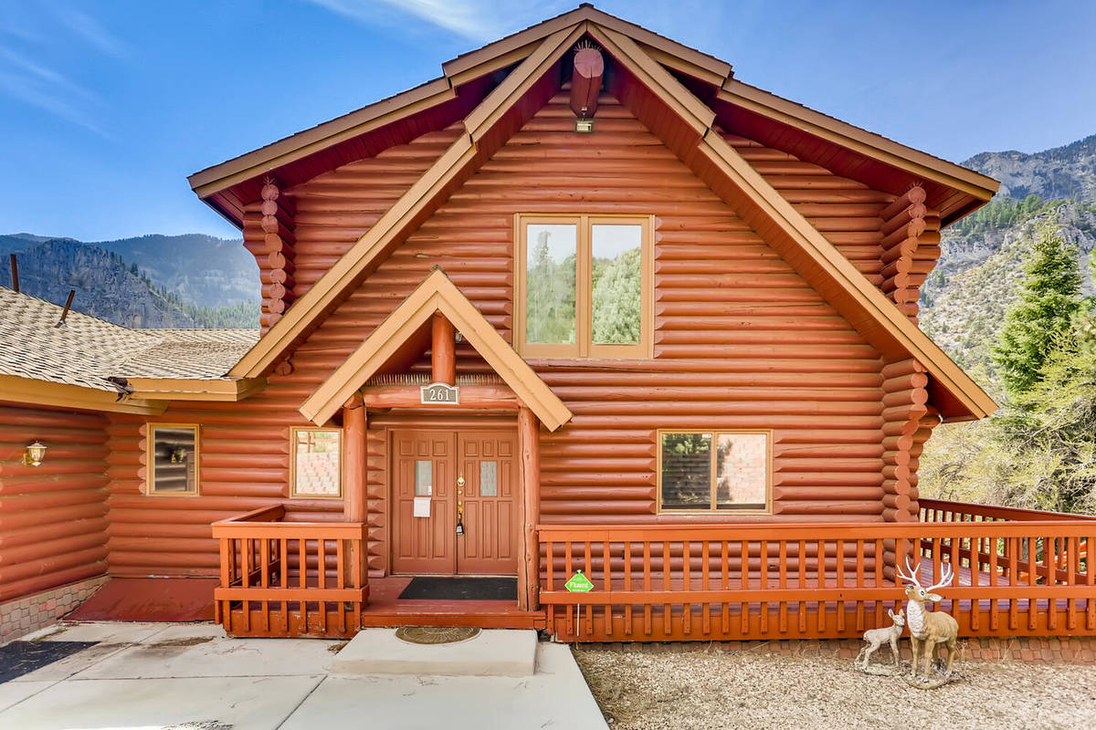 This 3,728-square-foot, custom log cabin on Mount Charleston at 261 Kris Kringle Road has been ...