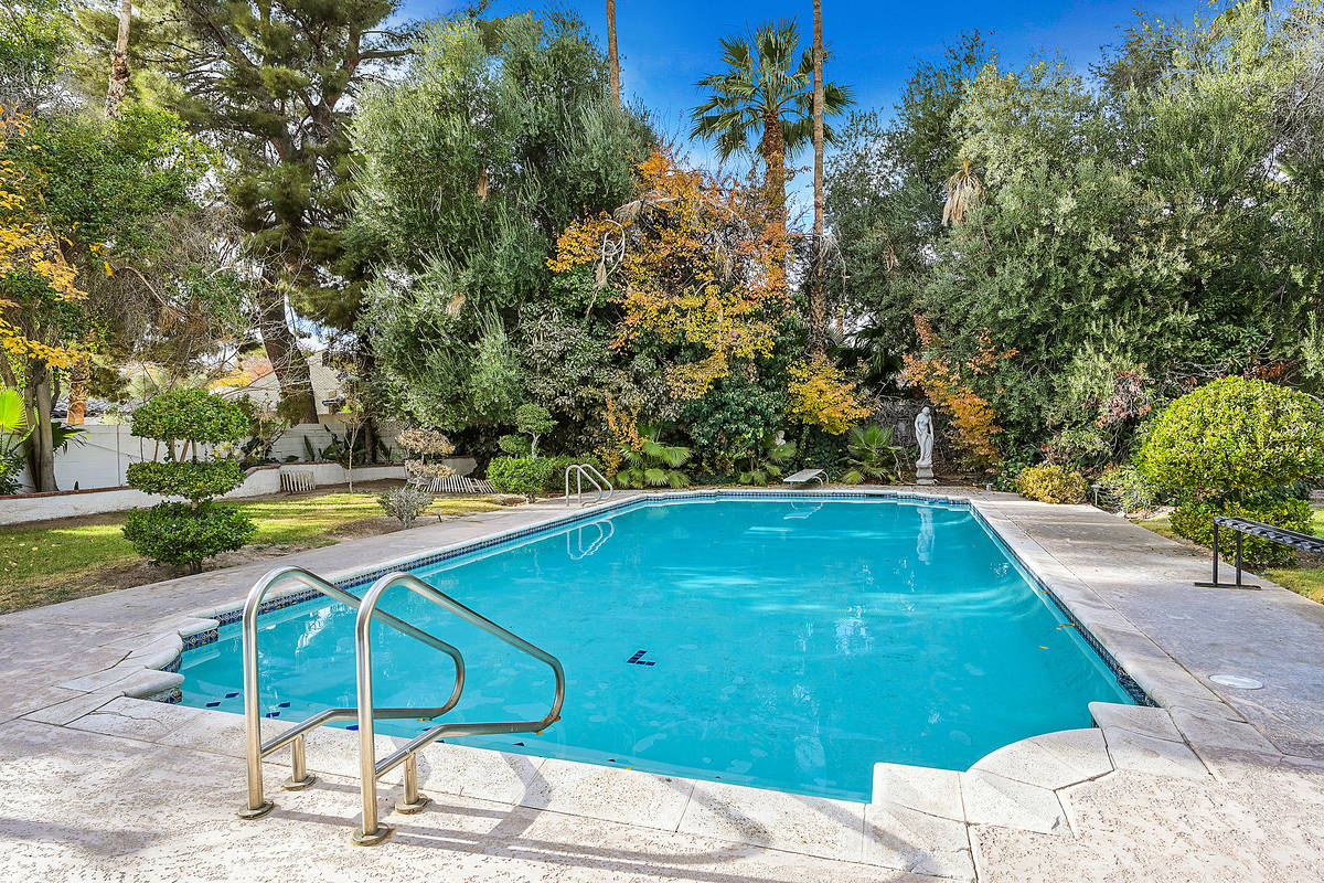 The backyard has a lap-style pool has mature landscaping, lush vegetation, grass, rose gardens, ...