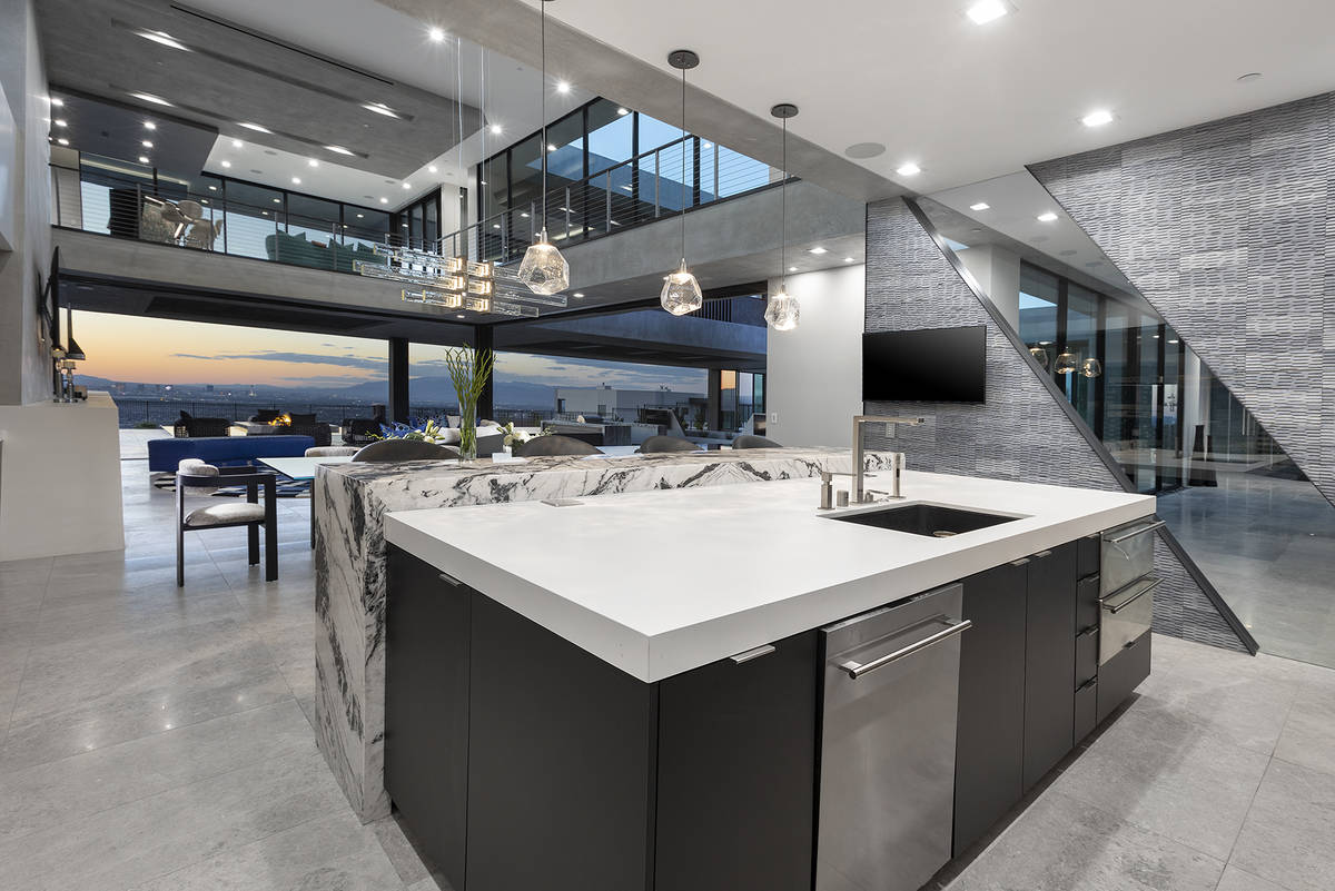 An angled natural stone wall borders the gourmet kitchen. (Synergy Sotheby's International Re ...