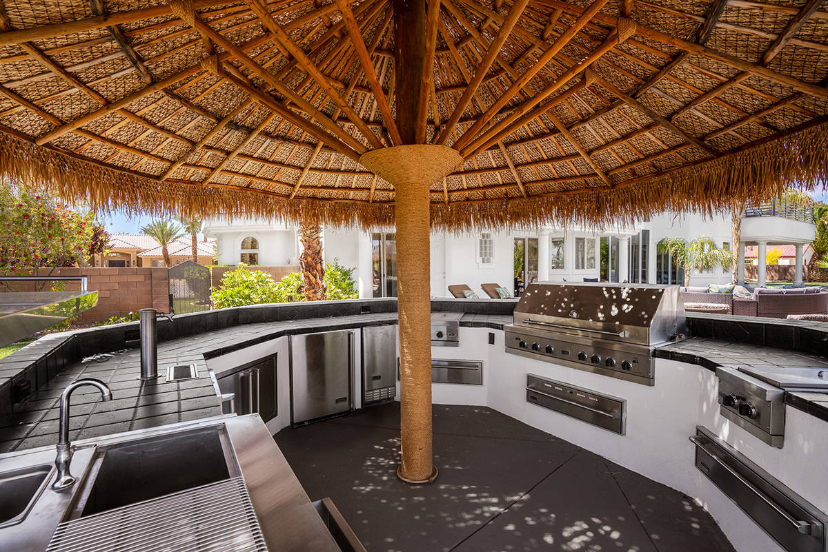 The outdoor kitchen features full round bar seating shaded by a large palapa umbrella. (Michael ...
