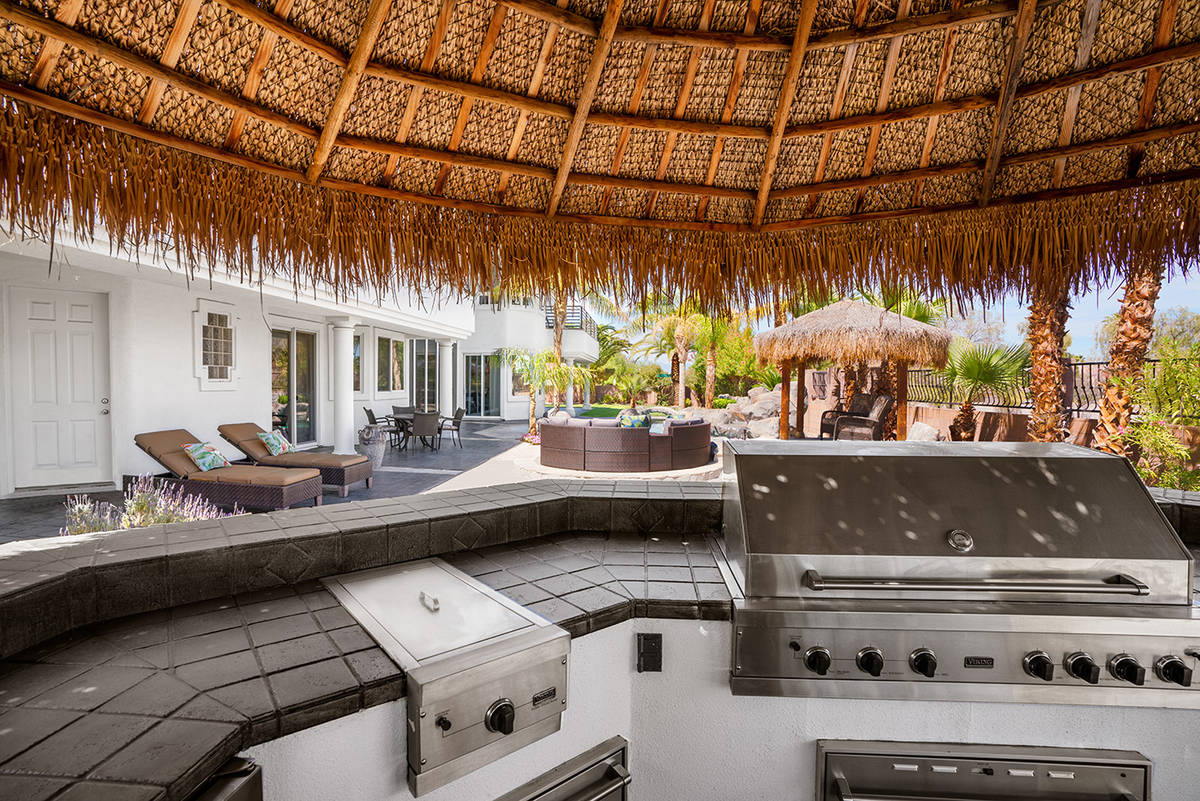 The integrated exterior U-shaped kitchen features a 60-inch grill and full round bar seating sh ...