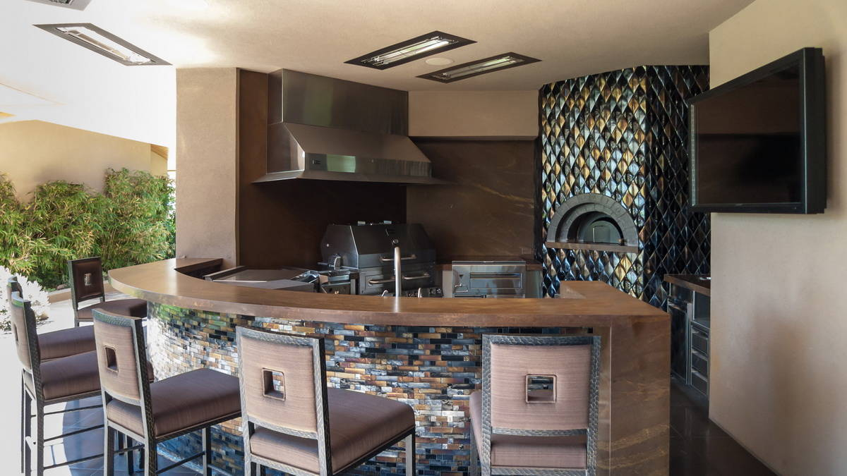 This luxury Summerlin home showcases a high-end outdoor kitchen that features a Kalamazoo grill ...
