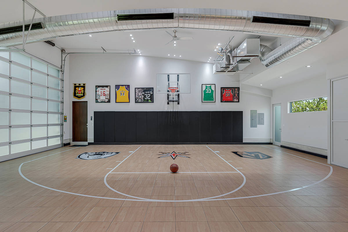 One of the home's three garages serves as a heated and cooled half-court basketball court. (The ...