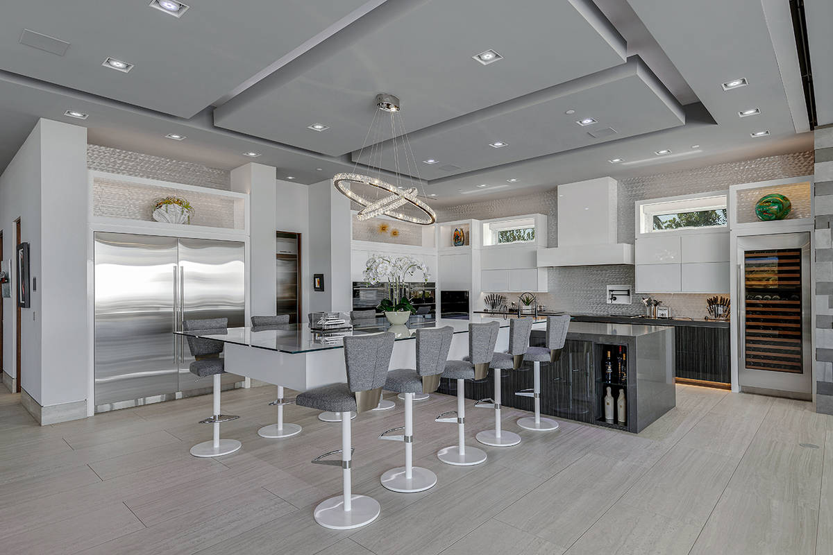 The kitchen, which has a pantry, extends outdoors to a second full kitchen and includes a teppa ...