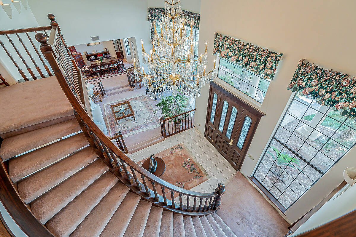 The entry showcases a five-tier chandelier. (BHHS)